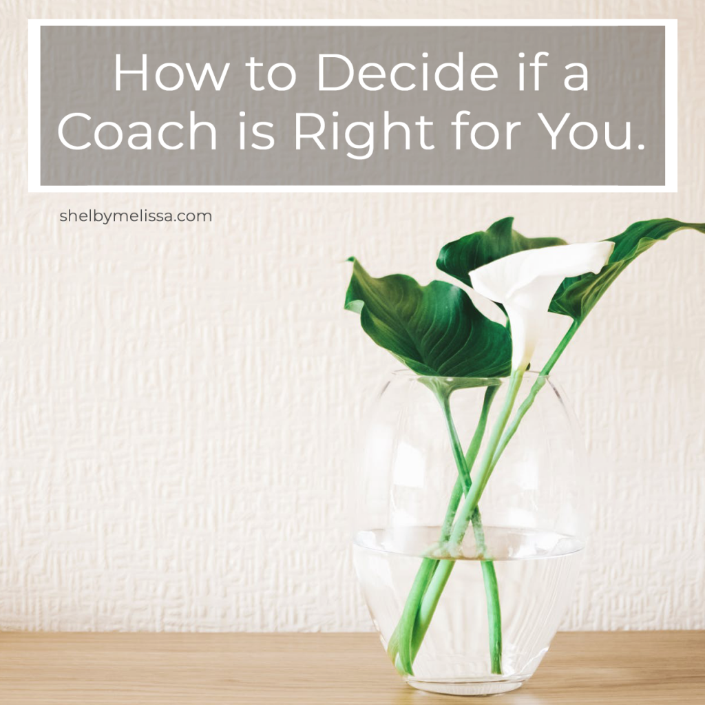 How to Decide if a Coach is Right for You. Image: white calla lily and leaves in a clear vase on a wooden surface.
